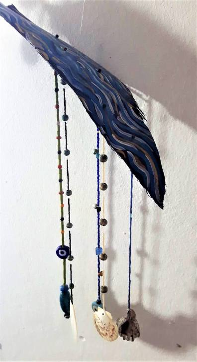 Wind bell with sea shells and symbols on palm leaf